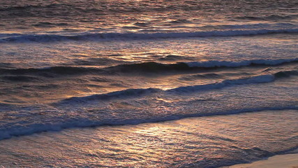 Colorful ocean water surface with surf during sunset