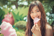Cute Thai girl is eating pink candyfloss with joy in vintage col