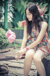 Cute Thai girl is sitting while holding pink candyfloss in vinta