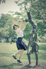 Cute Thai schoolgirl is jumping with a statue in the park in vin