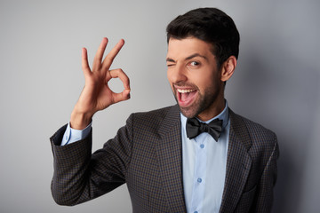 Smiling man winking and showing ok sign