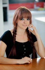 Rebellious teenager girl with red hair at home