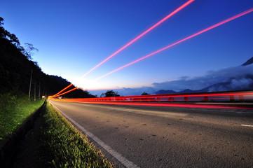 Light car trails in a road, twilight blue sky