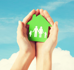 hands holding green house with family