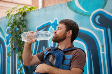 man drinking water from plastic bottles on background graffiti