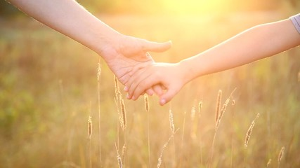 mother and child holding hands at sunset background