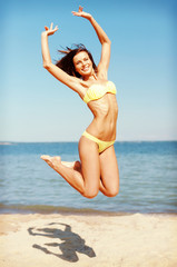 woman in bikini jumping on the beach