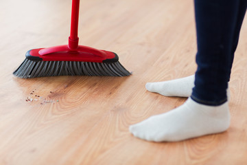 close up of woman legs with broom sweeping floor