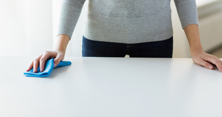 close up of woman cleaning table with cloth