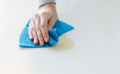 close up of hand cleaning table surface with cloth