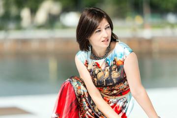 Model in dress posing on exterior set looking away
