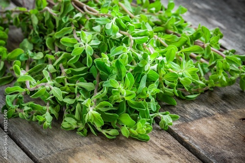 fresh raw green herb marjoram on a wooden table - 80325449