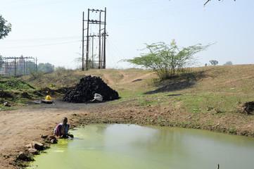 Boy washing hands on a puddle near Khajuraho on India
