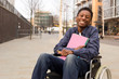 Leinwanddruck Bild - happy young disabled man in a wheelchair holding folders.