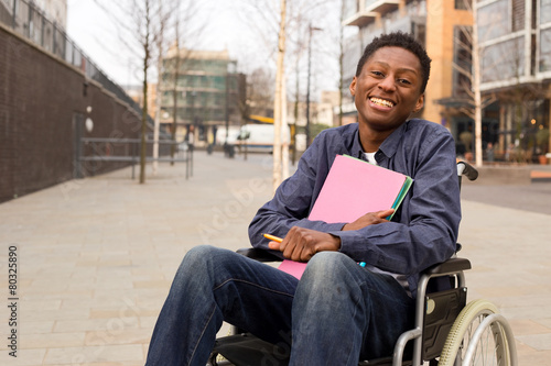 Leinwanddruck Bild happy young disabled man in a wheelchair holding folders.