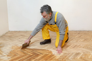 Varnishing of oak parquet floor, mature adult worker using tool