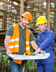 Confident Architect With Colleague Analyzing Blueprint At Constr