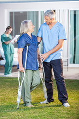 Male Nurse Assisting Senior Woman To Use Crutches