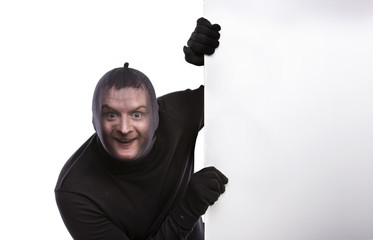 Thief in balaclava making funny faces, dressed in black.
