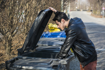 Attractive young man putting out rubbish