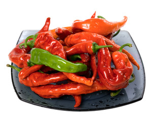 Red and green peppers on glass plate