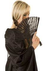 woman in black cloak side behind fan