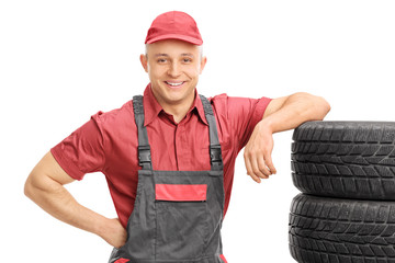 Young male mechanic leaning on a bunch of tires
