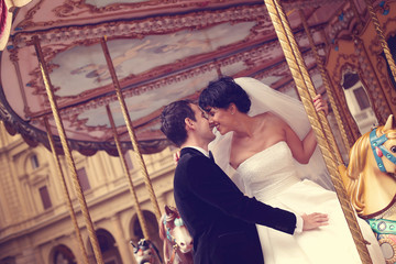 groom and bride kissing in a carousel