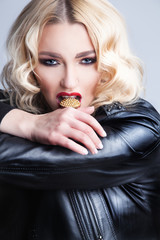 Sexy blond woman in black leather jacket with golden ring in her