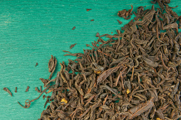 Tea leaves on wooden background