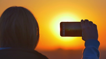 The young woman shot sunset (sunrise) with the phone