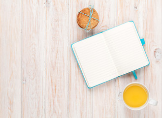 Cup of orange juice, gingerbread cookies and notepad