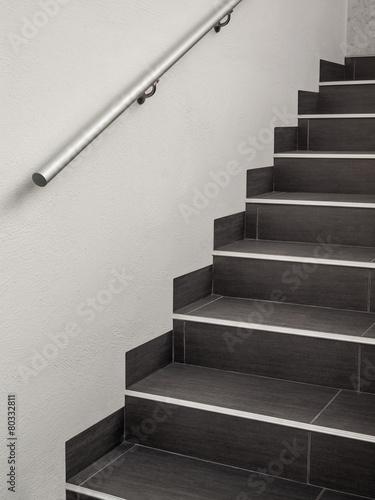 Leinwanddruck Bild Moderne gekachelte Treppe mit Handlauf aus Edelstahl