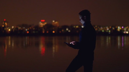 The man stand near lake and phone by night city lights