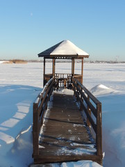 Wooden gazebo and planked footway by the river at winter