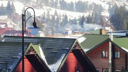 The smoke from the chimney on a background of the ski resort