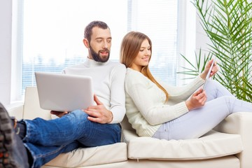 Life. Young couple relaxing on sofa with digital tablet and