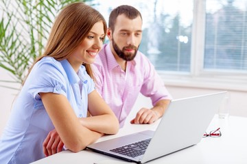 Laptop. Business team consisting of a young man and woman