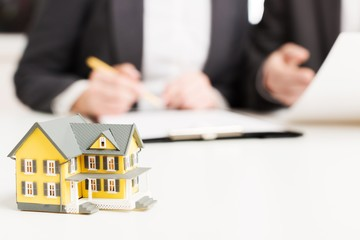 Agency. Businessman signs contract behind home architectural