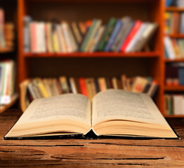 Open book on table on bookshelves background