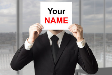 businessman hiding face behind sign your name
