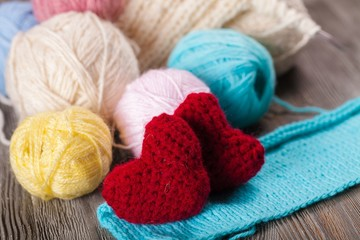 Crocheting. Crochet pink hearts  and yarn on wooden background