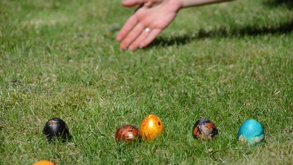 Hand countdown to start Easter egg game. Roll colorful eggs