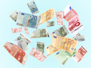 Flying Euro banknotes on blue background