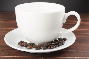 roasted coffee beans in coffee cup on wooden board with black  b