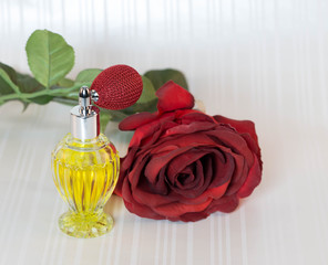 Perfume bottle with red atomizer and red rose