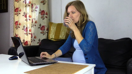 Worried pregnant business woman working near laptop drink water