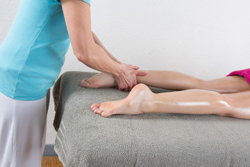 Beautiful young woman is ready for ankle's massage at  spa