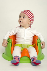 Adorable little boy relaxing in a toy chair ready for his dinner