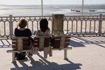 A rear view of people sitting on a bench at sea side